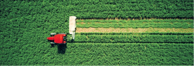 tractor mowing green field aerial view